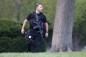 A member of the U.S. Secret Service Emergency Response Team (ERT) stands watch on the North Lawn at the White House in Washington, Thursday, Aug. 7, 2014. It's usually someone jumping over the White House fence that causes Secret Service agents patrolling the grounds to scramble. A toddler passing through slats in the gate caught the eyes of the gun-toting officers who are charged with protecting the president. (AP Photo/Charles Dharapak)