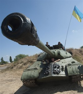 Ukrainian government soldiers drive their tank with a Ukrainian national flag in Donetsk region, eastern Ukraine, Saturday, Aug. 9, 2014. A top commander of the pro-Russia insurgency in eastern Ukraine said Saturday that Ukrainian forces have seized Krasnyi Luch a key town, leaving the rebel region's largest city of Donetsk surrounded. (AP Photo/Evgeniy Maloletka)