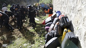 In this photo released by China's Xinhua News Agency, suitcases of tour bus passengers are piled up as rescuers work near an overturned bus after it fell off a 10-meter (30-foot) cliff in Nyemo County, southwest China's mountainous region of Tibet Saturday, Aug. 9, 2014. Xinhua reported the bus carrying about 40 people careened after it crashed in a pileup involving a sports utility vehicle and a pickup truck on a state road. Casualty details were not immediately known. (AP Photo/Xinhua, Chogo) NO SALES
