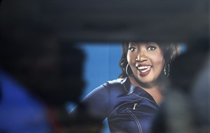 """A taxi with passengers drives past a billboard featuring Sophie Ndaba, an actor who played the Queen Moroka character in """"Generations,"""" soap opera displayed on the street in Soweto, South Africa, Wednesday, Aug. 20, 2014. """"Generations,"""" a hugely popular soap opera in South Africa, first aired in 1993, a year before the nation's first all-race elections ended apartheid. Now the future of this television staple followed by millions is up in the air. (AP Photo/Themba Hadebe)"""