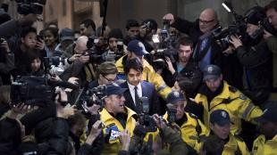 Former CBC Radio host Jian Ghomeshi, centre, is escorted out of court after being released on bail in Toronto on Nov. 26, 2014. THE CANADIAN PRESS/Darren Calabrese