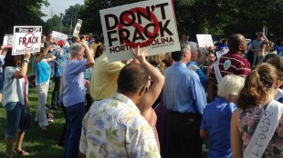 FILE - In this Aug. 20, 2014, file photo, protesters gather and hold signs before a hearing on proposed rules for hydraulic fracturing, or fracking, oil and gas drilling, in Raleigh, N.C. A judge has halted the approval of fracking operations in North Carolina until a higher court weighs in on the legality of the appointment of several boards that manage state resources and the environment. (AP Photo/Jonathan Drew, File)