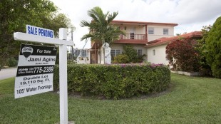 """FILE - In this Thursday, Jan. 8, 2015 file photo, a """"sale pending"""" sign is posted atop a realty sign in front of a home in Surfside, Fla. The National Association of Realtors releases its January report on pending home sales, which are seen as a barometer of future purchases, on Thursday, May 28, 2015. (AP Photo/Wilfredo Lee, File)"""