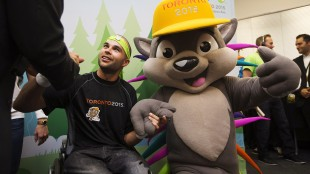 Wheelchair basketball Paralympic gold medallist and Parapan Am bronze medallist Tyler Miller, left, helps unveil Pachi the porcupine as the new mascot for the Toronto 2015 Pan Am/Parapan Am Games, July 17, 2013. THE CANADIAN PRESS/Michelle Siu