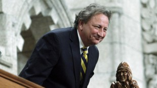 Eugene Melnyk, owner of the NHL's Ottawa Senators, stands in the visitors gallery as he is recognized in the House of Commons at the conclusion of Question Period on Parliament Hill, in Ottawa Tuesday, March 4, 2014. Melnyk urgently needs a liver transplant and the NHL club has put out a call for potential ``live donor.'' THE CANADIAN PRESS/Fred Chartrand