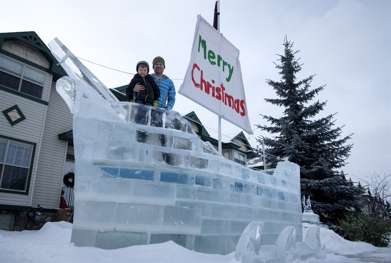 Donnie White And His Four Year Old Son Mateo Pose With The Ice Ship Built On Their Front Yard Using Frozen Blocks Of From A Nearby Pond In Red